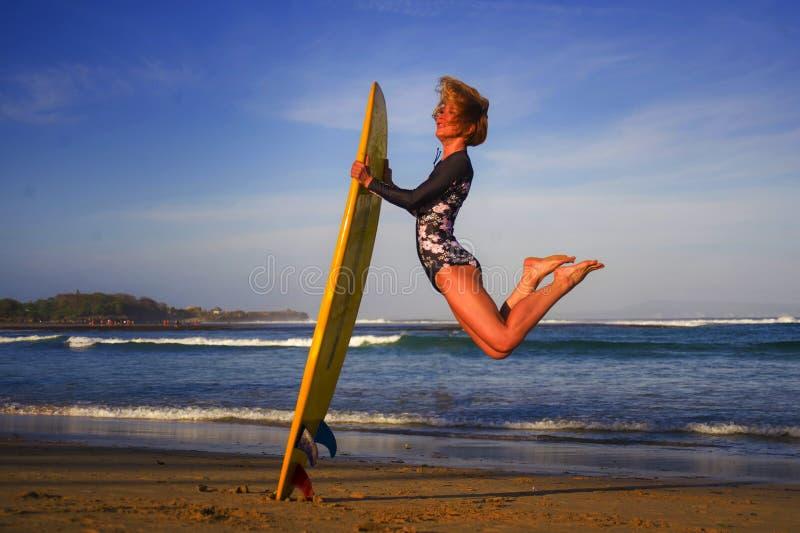 跳高在天空中的年轻愉快和可爱的冲浪者女孩拿着水橇板在冲浪在美丽的热带海滩前享用 库存图片