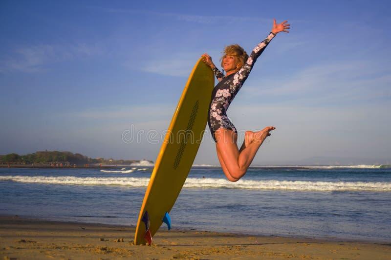 跳高在天空中的年轻愉快和可爱的冲浪者女孩拿着水橇板在冲浪在美丽的热带海滩前享用 图库摄影