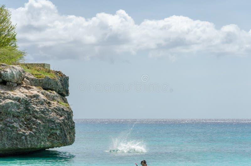 跳从岩石的游人在盛大Knip海滩 库存图片