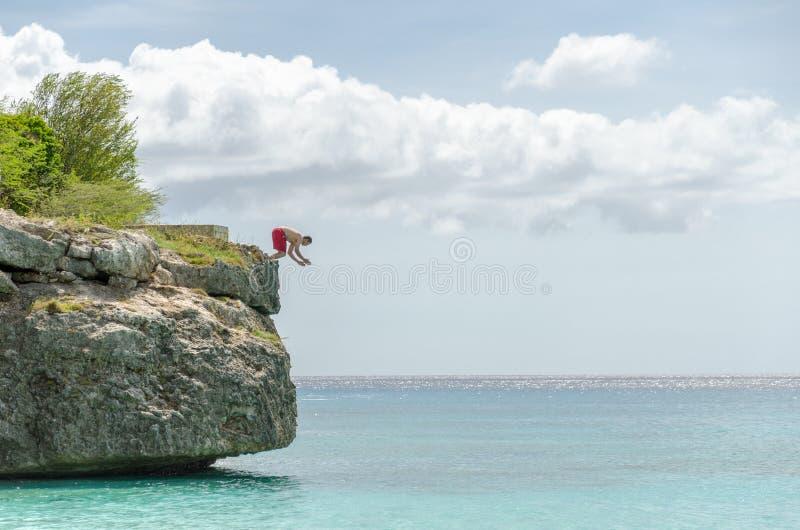 跳从岩石的游人在盛大Knip海滩 免版税库存图片