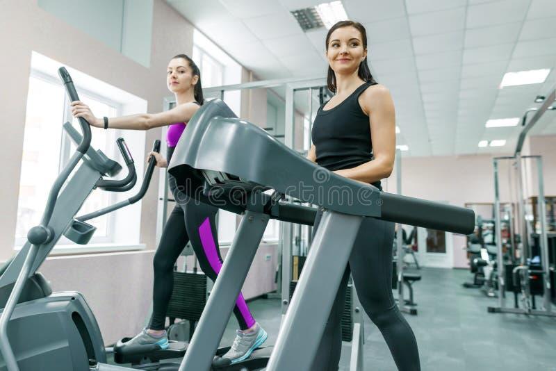 踏车的两名年轻健身健康妇女在体育现代健身房 健身,体育,训练,人概念 免版税图库摄影