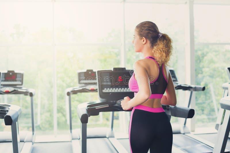 踏车的可爱的妇女在健身俱乐部,健康生活方式 免版税库存图片
