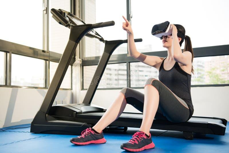 踏车的秀丽亚洲妇女基于有VR耳机的 免版税图库摄影