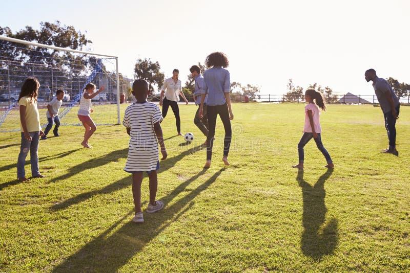踢与他们的孩子的两个年轻家庭橄榄球 库存图片