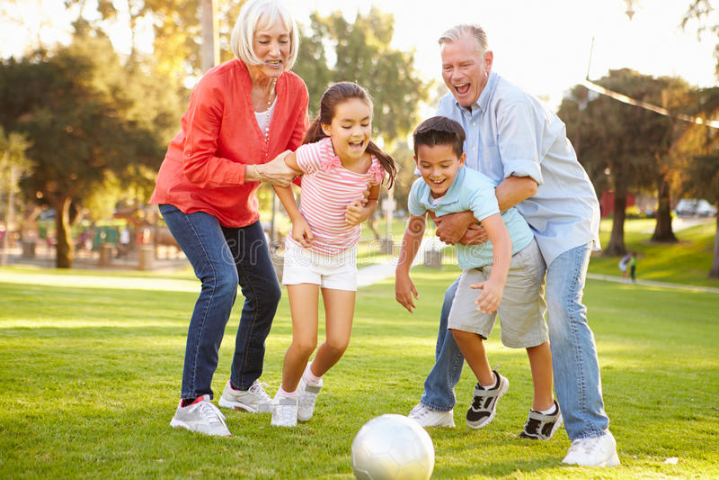踢与孙的祖父母足球在公园 免版税库存图片