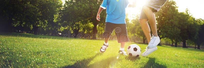 踢与他的父亲概念的小男孩足球 图库摄影
