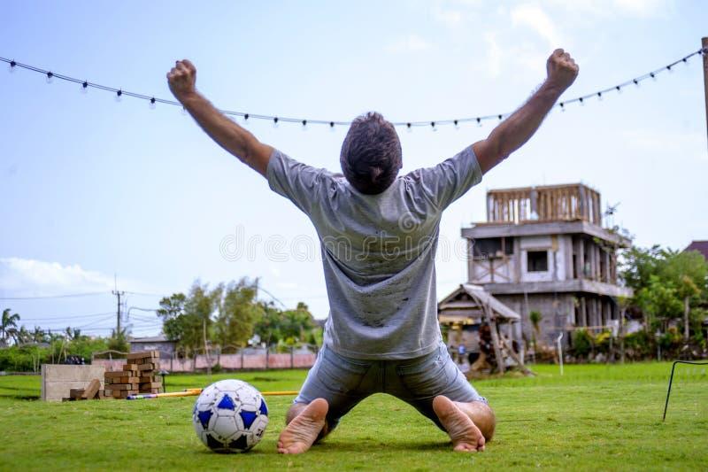 踢在他的膝盖的年轻可爱和愉快的人橄榄球在看齐专业足球运动员姿态的草地,当cele 免版税库存照片