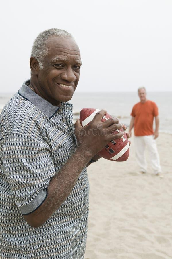 踢在海滩的两名老人橄榄球 免版税库存照片