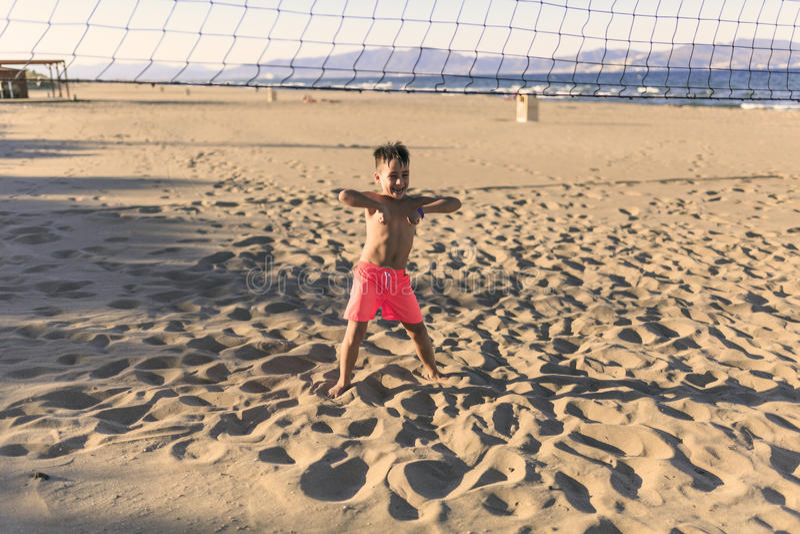 踢在海滩的孩子橄榄球 图库摄影