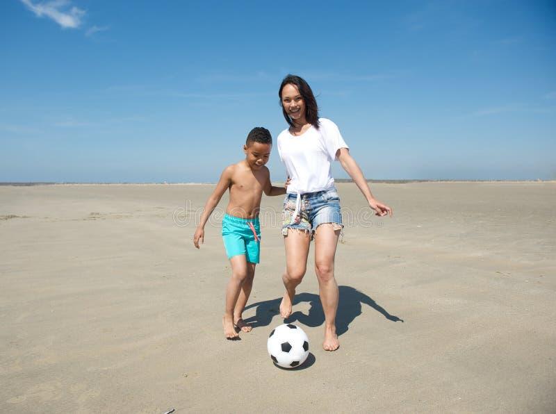 踢在海滩的母亲和儿子橄榄球 库存图片