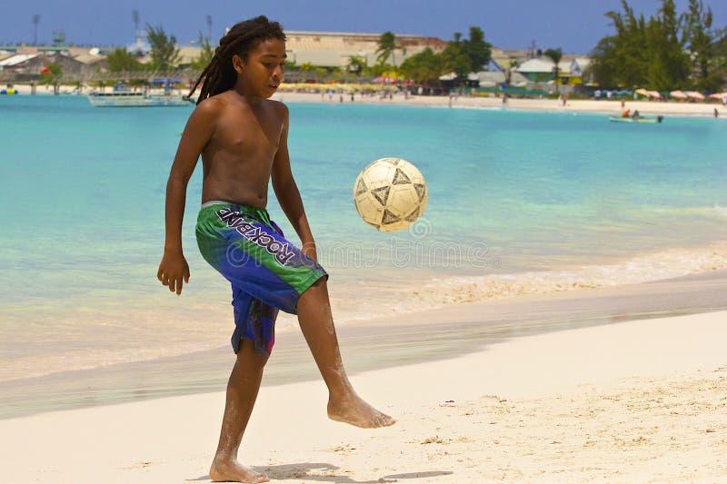 踢在海滩的年轻男孩橄榄球在巴巴多斯,加勒比 免版税库存照片