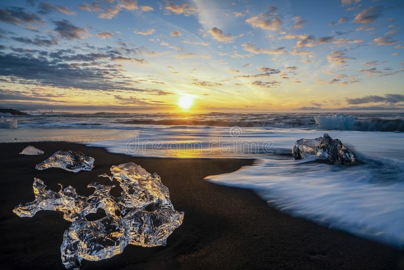 踢开冰块的发怒的波浪在金刚石海滩的日出 免版税库存图片