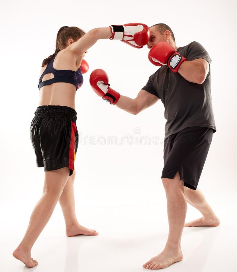踢拳手女孩和她的教练 图库摄影