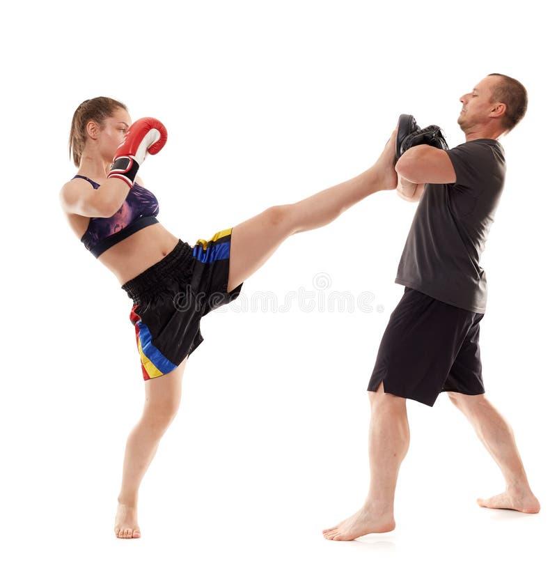 踢拳手女孩和她的教练 免版税库存照片