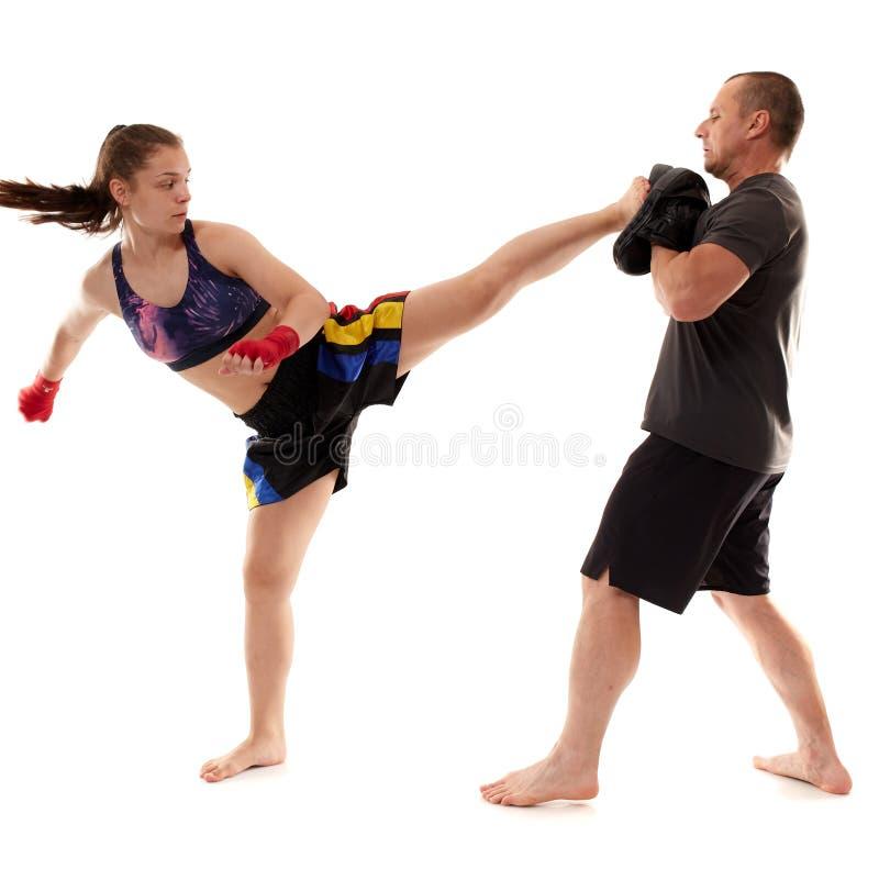 踢拳手女孩和她的教练 免版税图库摄影