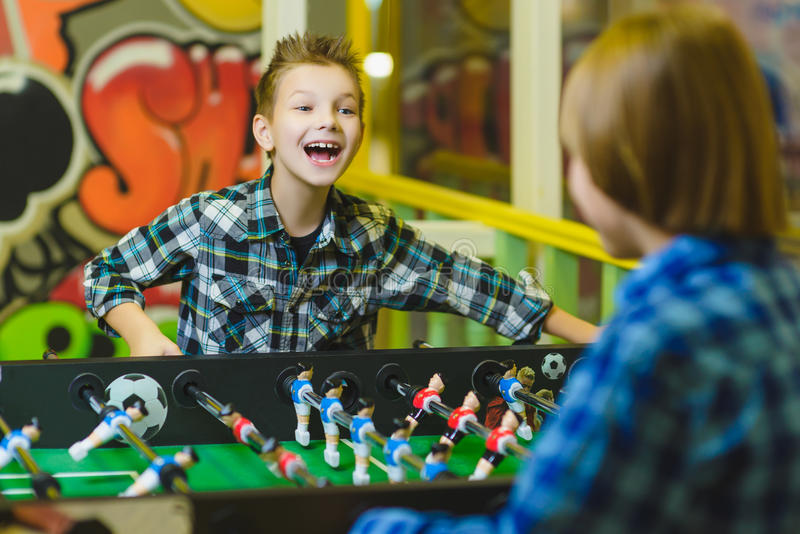 踢桌橄榄球的愉快的男孩在儿童居室 免版税库存图片