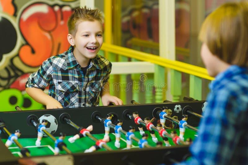 踢桌橄榄球的愉快的男孩在儿童居室 图库摄影