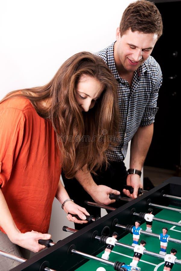 踢桌橄榄球的朋友 免版税库存照片