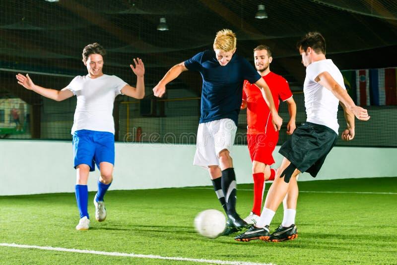 踢橄榄球或足球的小组室内 库存图片