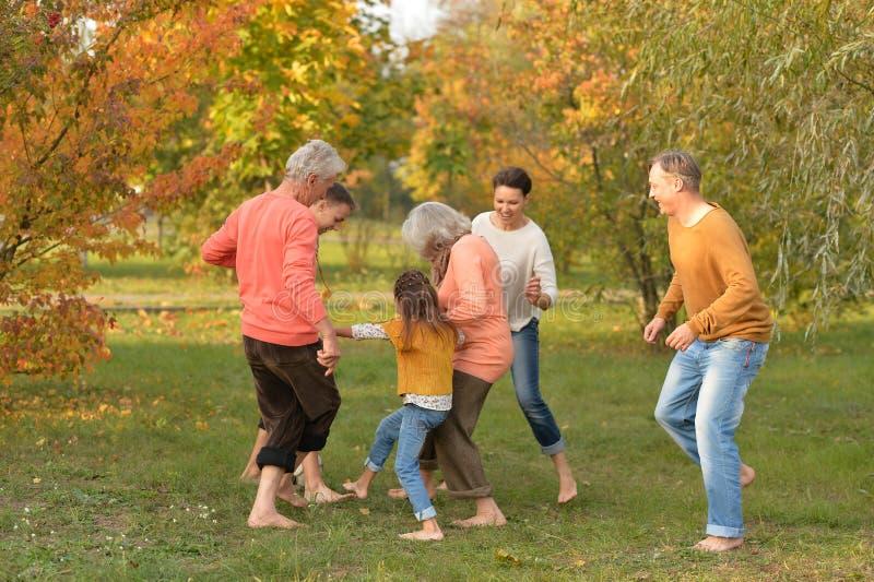 踢橄榄球的大幸福家庭画象在公园 图库摄影