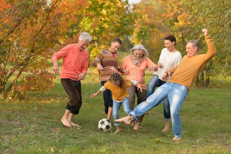 踢橄榄球的大愉快的家庭在秋天公园 库存图片