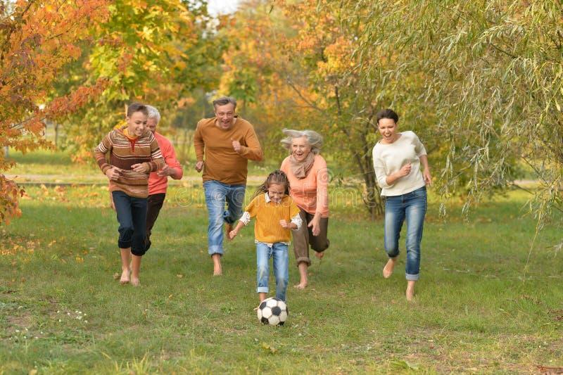 踢橄榄球的大愉快的家庭画象在公园 库存照片