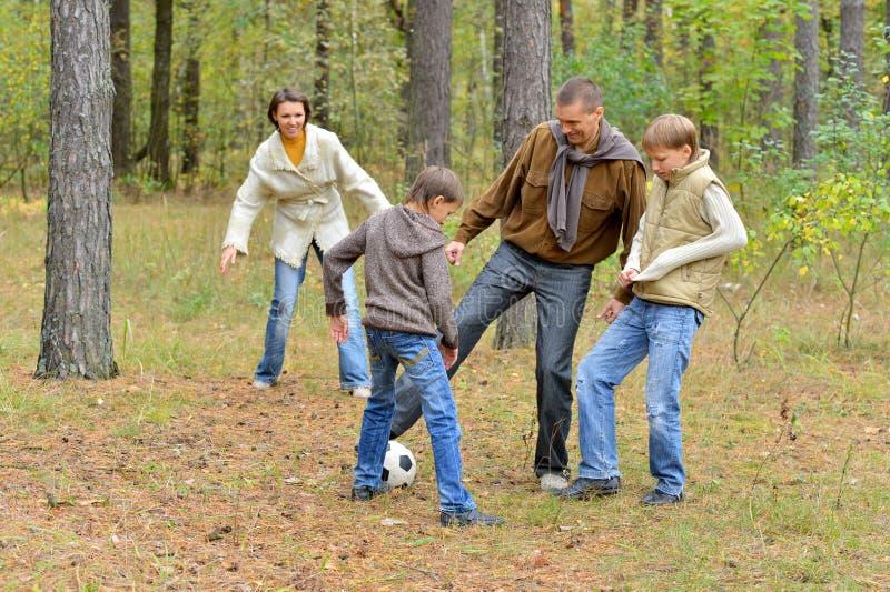 踢橄榄球的大愉快的家庭画象在公园 库存图片