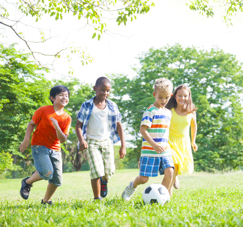 踢橄榄球的孩子在公园 库存照片