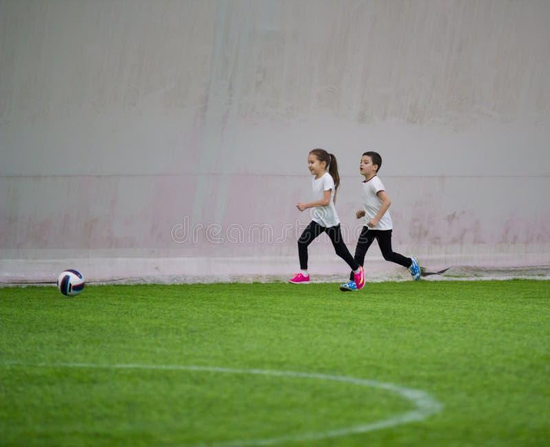 踢橄榄球的孩子户内 女孩和男孩使用 免版税库存图片