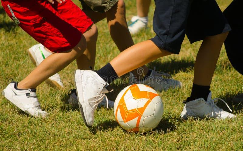 踢橄榄球的少年 免版税库存照片