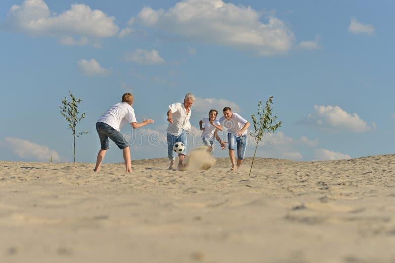 踢橄榄球的快乐的活跃家庭 免版税图库摄影