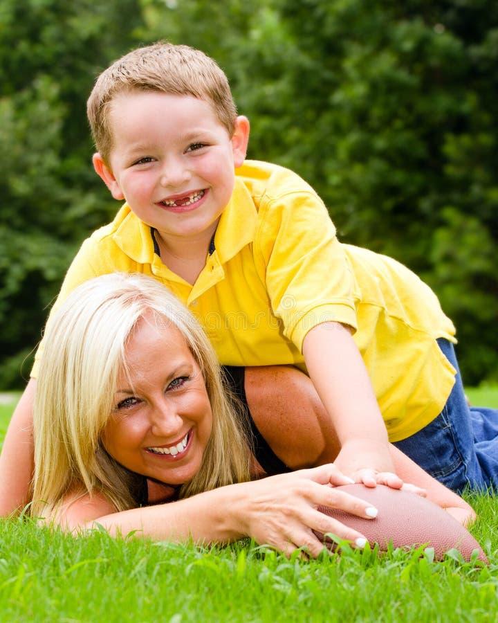 踢橄榄球的母亲和儿子户外 库存图片