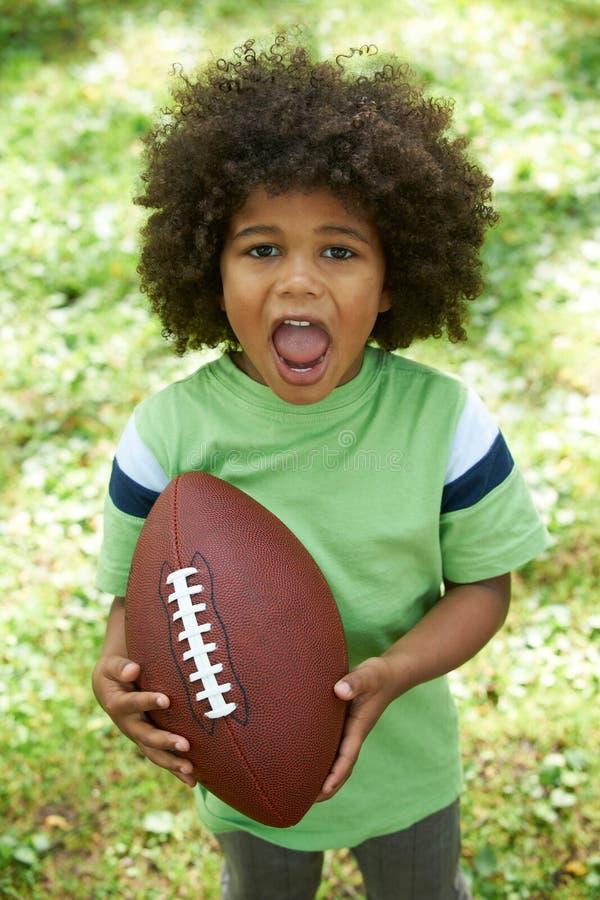 踢橄榄球的激动的年轻男孩在公园 图库摄影