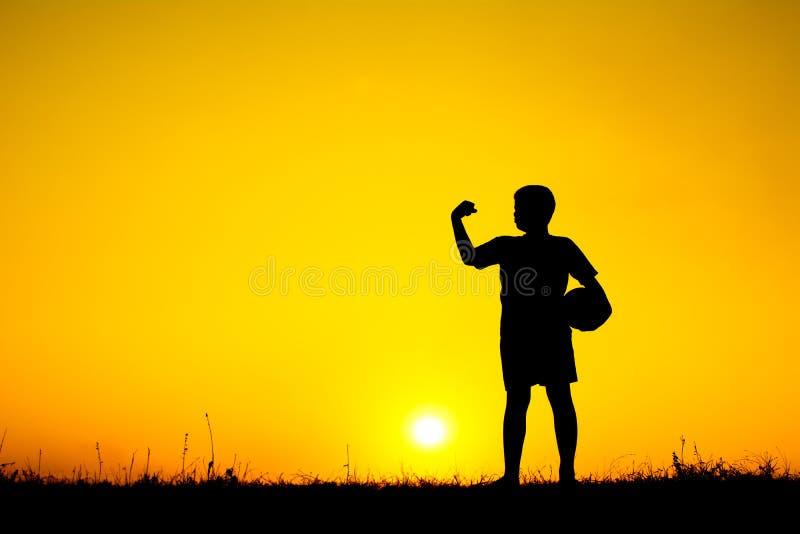 踢橄榄球的男孩剪影在天空日落期间 免版税库存图片