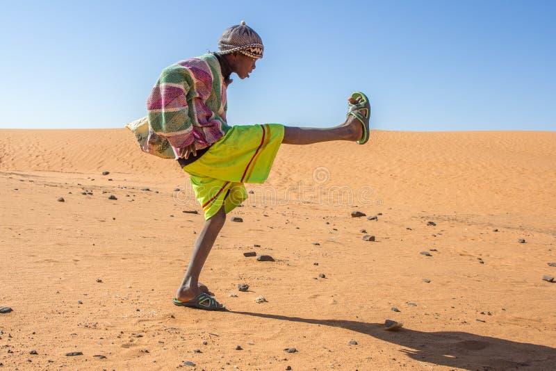 踢橄榄球的年轻苏丹人男孩 免版税库存照片