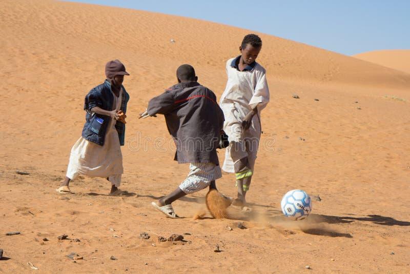 踢橄榄球的年轻苏丹人男孩 库存照片