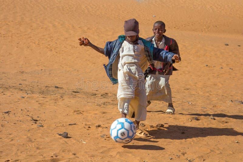 踢橄榄球的年轻苏丹人男孩 免版税库存图片