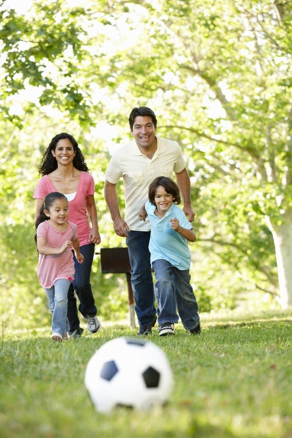 踢橄榄球的年轻西班牙家庭在公园 免版税库存图片