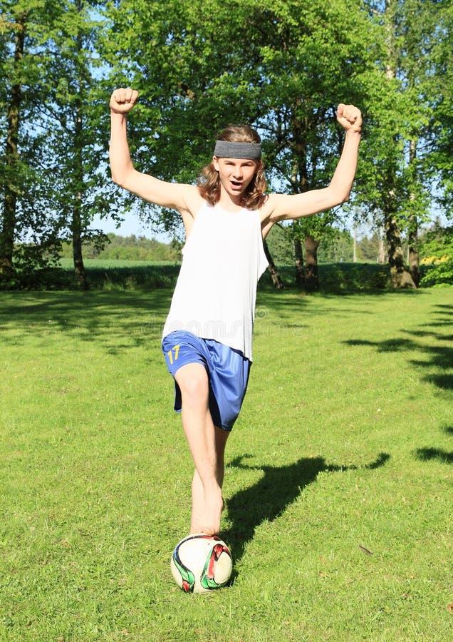 踢橄榄球-优胜者的少年 免版税图库摄影