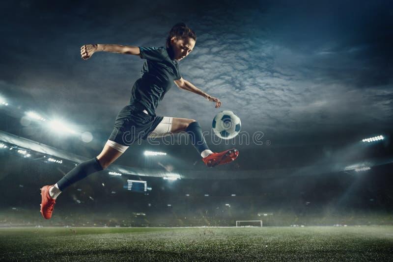 踢球的女性足球运动员在体育场 免版税库存图片