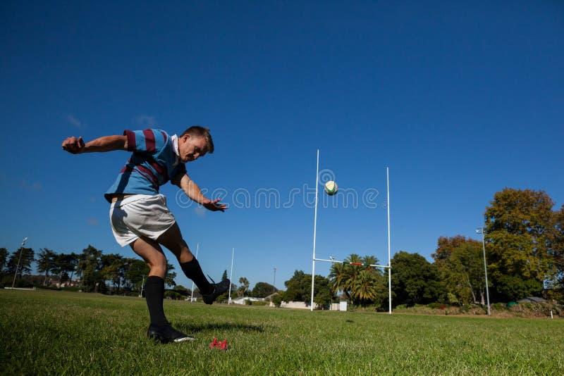 踢目标的橄榄球球员球反对清楚的蓝天 免版税库存图片