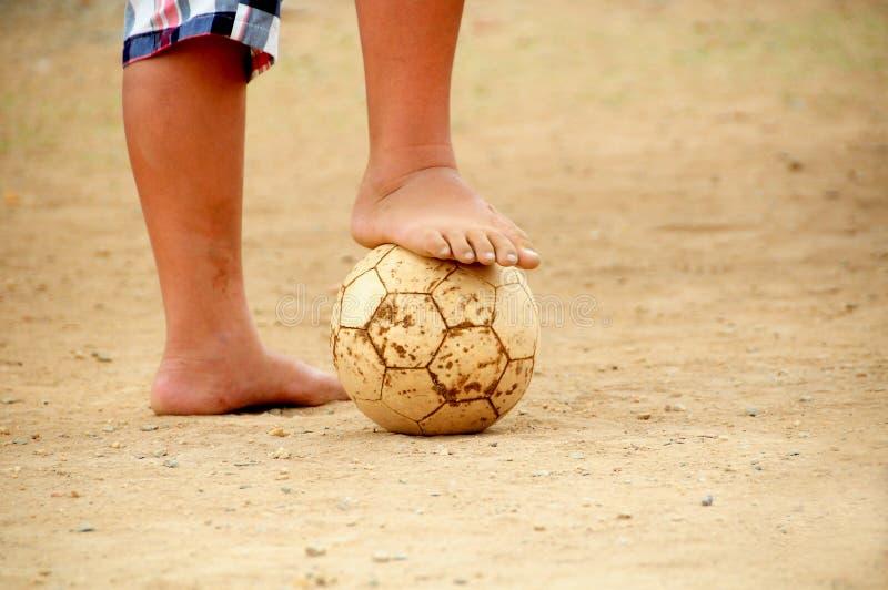 踢赤足橄榄球的可怜的孩子 免版税库存照片