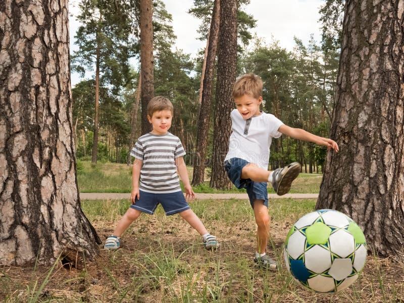 踢足球的孩子室外 孩子的娱乐活动 免版税库存照片