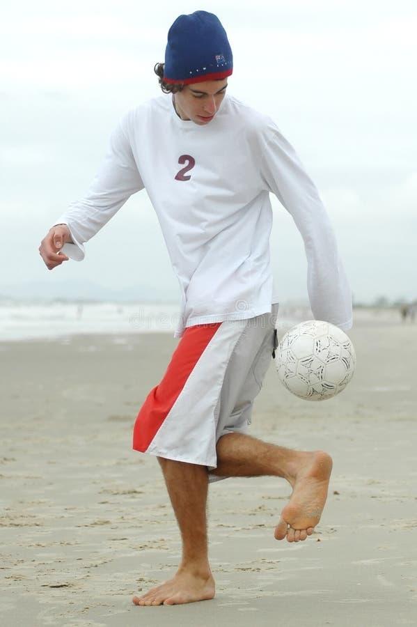 踢足球的海滩人 免版税库存图片