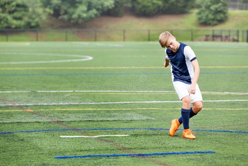 踢足球的男孩-踢了球 图库摄影