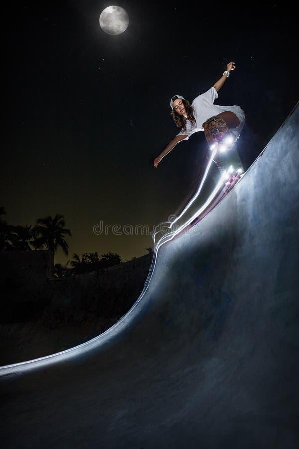踩滑板在夜冰鞋公园的射击女孩 图库摄影