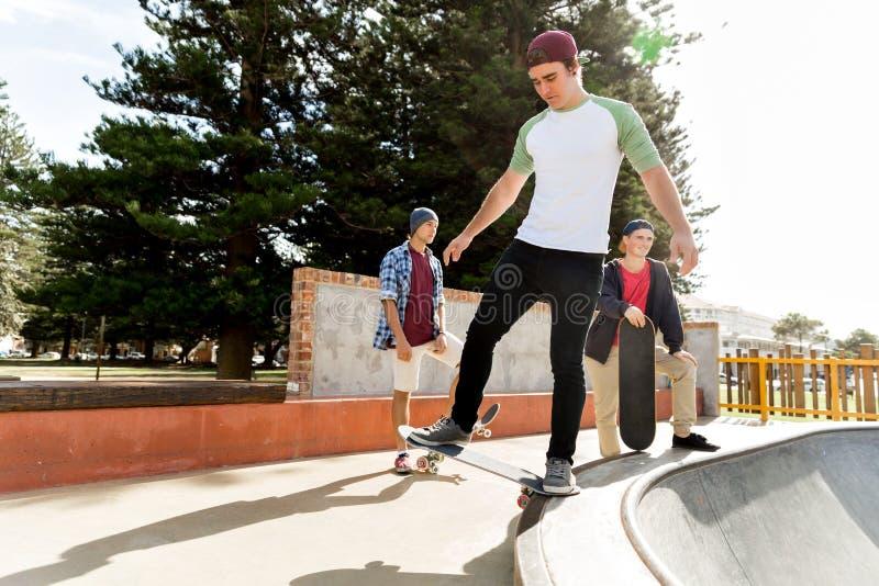 踩滑板的十几岁的男孩户外 免版税库存照片