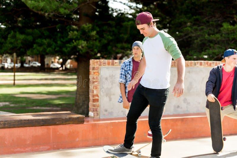 踩滑板的十几岁的男孩户外 图库摄影