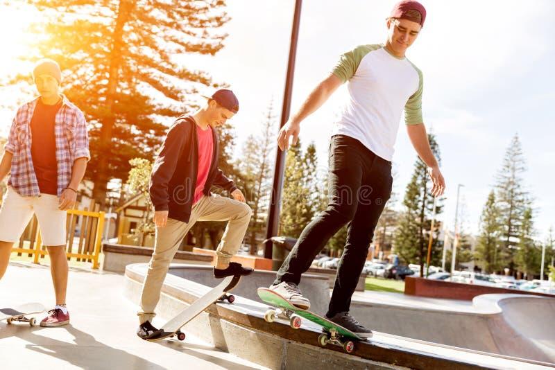 踩滑板的十几岁的男孩户外 库存照片