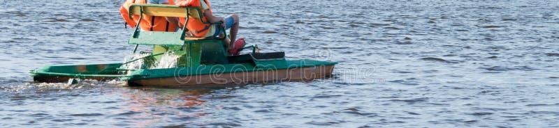 踩的踏板一个的孩子的脚橡胶拖鞋的在水,长的照片的一艘筏 免版税库存照片